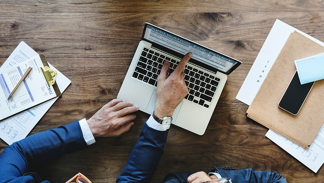Gente trabajando sobre una mesa con un ordenador